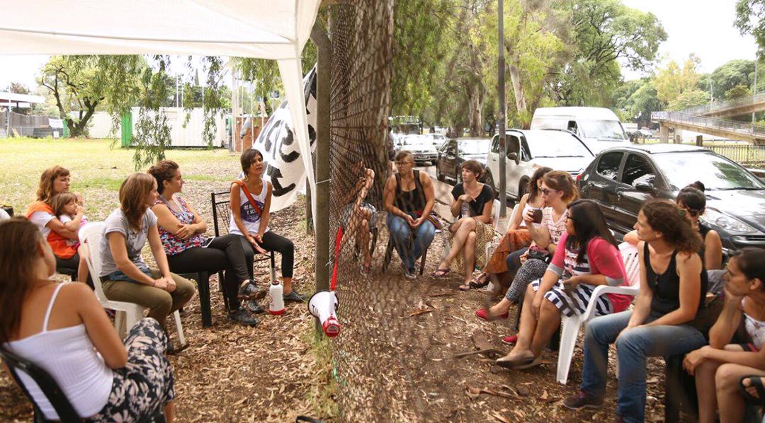 Visita de Trabajadoras de CyU a sus pares del INTI, separadas por la enrejado del predio durante el acampe que se realiza en el organismo debido a los más de 250 despidos. Foto: Trabajadoras del INTI